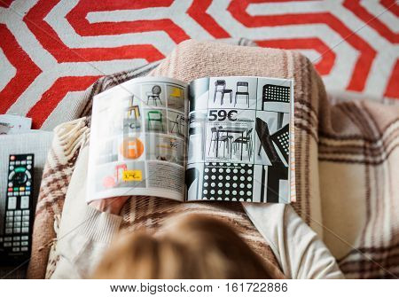 PARIS FRANCE - AUGUST 24 2014: View from above of woman reading IKEA Catalogue before buying chairs for her new house. The catalogue is published annually by the Swedish home furnishing retailer