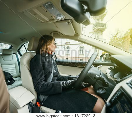Side view of elegant woman being careful on the road while driving confident a car in city enjoying the traffic and good radio station music