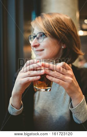 Fashion elegant woman drinking darjeeling black green orange pekoe tea from glass cup in cozy romantic cafe