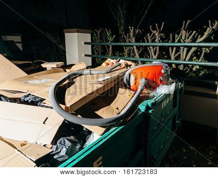 Large waste container in urban city with old furniture and home appliance in Frenc city at night