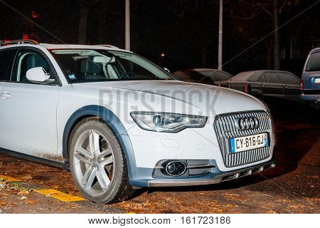 STRASBOURG FRANCE - DEC 6 2017: White Audi A6 Allroad car parked at night in the city