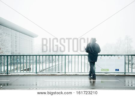STRASBOURG FRANCE - DEC 7 2016: Man taking photographs on a snowy day of the Agora Council of Europe building