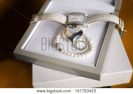 Ladies wrist watch pearl necklace and a heart shape laid in the open box closeup indoor shot