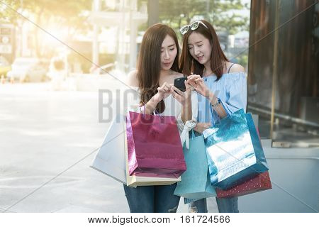 two young aisin woman using her smartphone and hold shopping bag while doing some shopping in a street shopping mall vintage tone and outdoor.