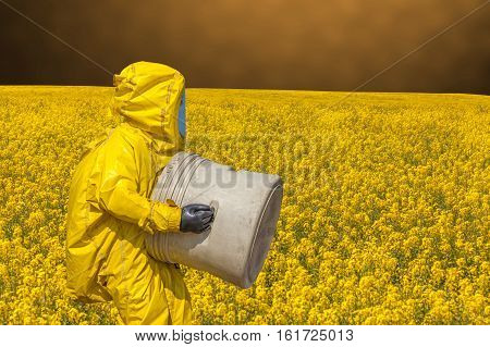 View of yellow rape field and men in protective hazmat suit