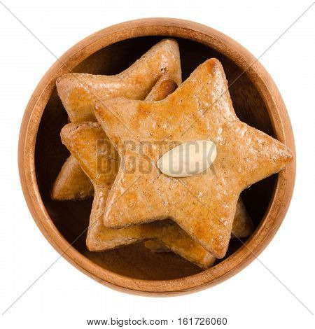 Gingerbread stars in wooden bowl. Sweet baked goods. Brown, flat and star-shaped with an almond half on top. Also ginger biscuit, nut or snap. Isolated macro food photo close up from above over white.