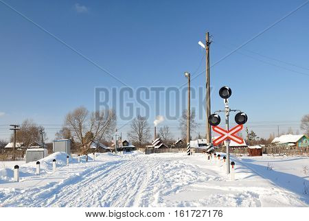 Unguarded railway crossing in the winter. Countryside.