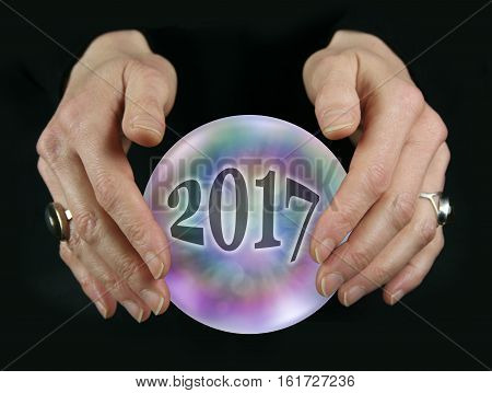 What will 2017 bring - Crystal Ball reading showing a 2017 inside a colorful translucent crystal ball between female hovering hands on a black background