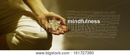 Mindfulness Meditation Word Cloud Banner - Female sitting in Lotus Position on left side with sunlight streaming in holding a Merkabah crystal meditating and a mindfulness word cloud on right side