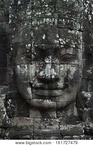 A vertical photographic image of a large sculpted stone face of the Buddha at Bayon Temple in Angkor Thom which is close to Angkor Wat near Siem Reap in Cambodia.