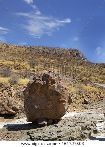 A large circular Boudr resting at the base of a hill in Damaraland , Namibia, Southern Africa