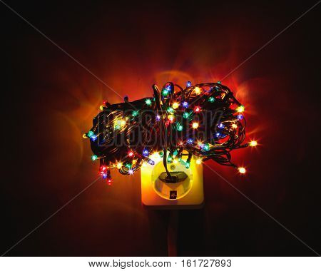 Christmas garland lights bundle on power socket, electricity concept