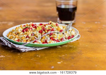 Warm salad with roasted chickpea, couscous, pomegranate seeds, lemon zest and almond nut flakes on a plate, selective focus