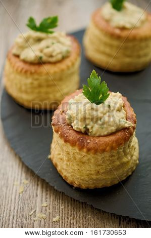 Puff pastry bouchees dough cups filled with tuna spread and garnished with parsley. Concept of amuse bouche. Selective focus on front parsley leaf.