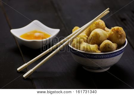 Chinese toffee bananas golden brown deep fried with caramel dipping sauce in white bowl and with chopsticks on side.