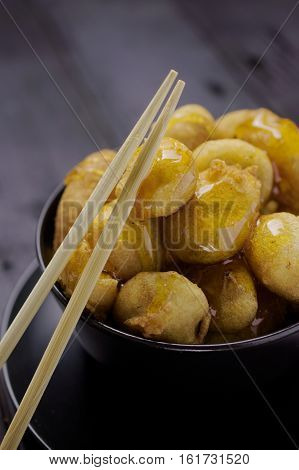 Chinese toffee bananas golden brown deep fried caramelized in black bowl with chopsticks.