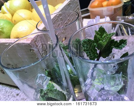 Making drinks cocktails or mojitos at bar for holiday party closeup on empty glasses with ice and fresh mint leaves garnish with lemons and oranges citrus ingredients in the background