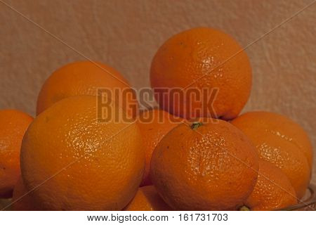 Oranges and tangerines. Many oranges and tangerines in a crystal vase on a light background