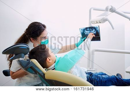 Doctor dentist and child in the office watching an x-ray. Dental treatment.