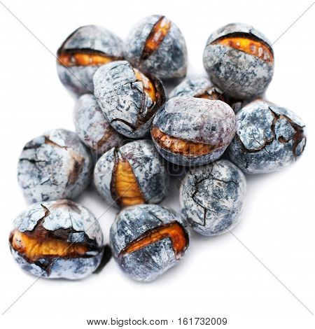 Roasted chestnuts isolated on white background close up. Heap of grilled edible chestnut