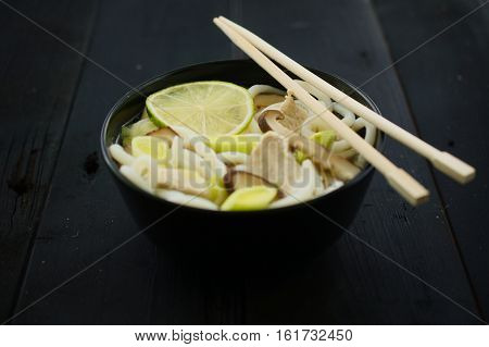 Japanese soup with udon noodles mushrooms leeks and lime. Concept of eating. Selective focus on front mushroom.