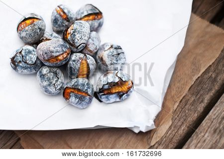 Roasted chestnuts served on white and brown craft paper with copy space. Delicious grilled chestnuts on old wooden table close up