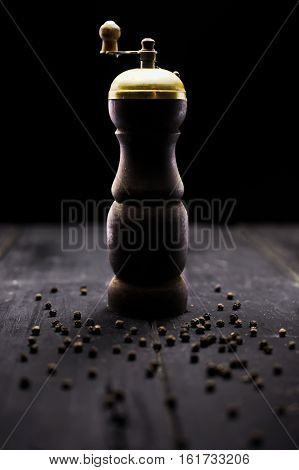 Old rustic antique pepper and salt spice grinder on wood boards. Selective focus on the grinder.