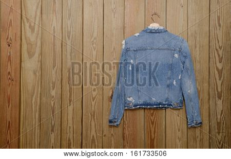 A blue denim jean shirt ,jacket is on clothes-hanger on wooden background