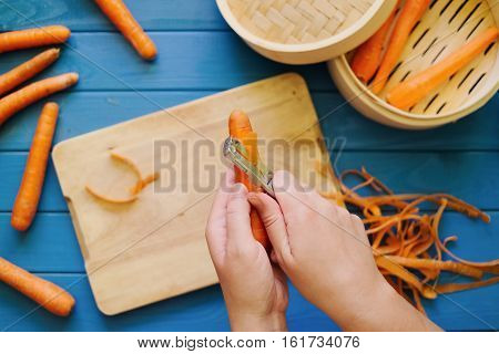 female hands peeling an orange carrot on blue background. Concept of healthy food preparation. Peeled carrots in steamer. Hands in frame. Top down view. Flat lay.