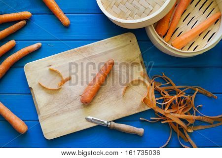 Peeled orange carrot on wood cutting board on blue background. Peels peeler and bamboo steamer. Concept of preparation of baby food. Top down. Flat lay.