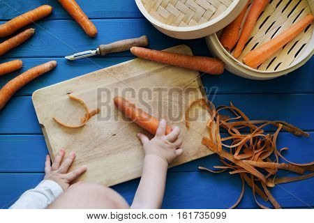 Small baby reaching for a carrot. Peeled and unpeeled carrots. Bamboo food steamer. Baby food preparation concept. Flat Lay. Top View. Hands in frame.