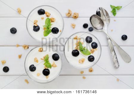 Delicious homemade dessert granola and blueberry yogurt parfait in glass with mint on white wood boards. Concept of light dessert. Top down view. Flat lay. Selective focus.