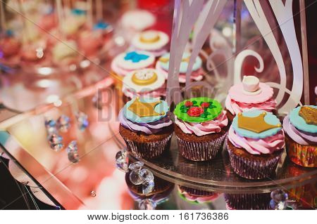 Beautiful multicolored decorated baked sweet tasty candy bar dessert on kids children party with happy people around, catering banquet table