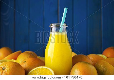 Freshly squeezed organic orange juice in bottle with colored straw and ripe organic oranges oranges agains blue wood boards background. Selective focus on straw. Concept of healthy lving. Concept of organic food. Concept of detox.