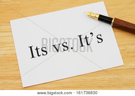 Learning to use proper grammar A white card on a desk with a pen with words Its vs It's