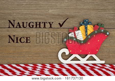 Old fashion Christmas message A retro Christmas sleigh on weathered wood background with text Naughty and Nice