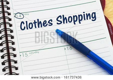 Planning your shopping trip A day planner with blue pen with text Clothes Shopping