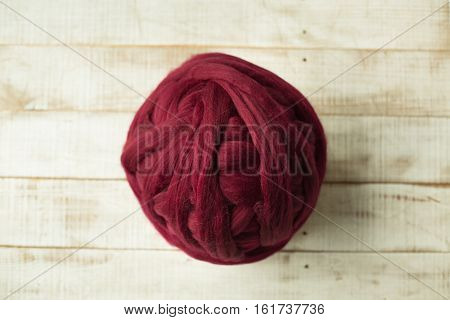 Red merino wool ball on wooden background