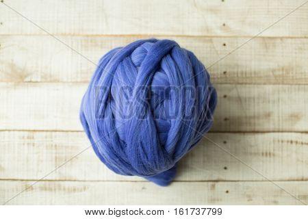 Blue merino wool ball on wooden background