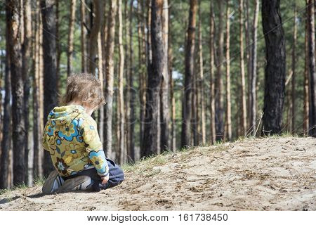 In the summer Little upset girl kneeling in the woods near a hill.