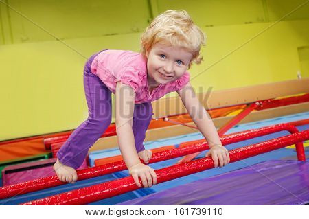 Portrait of white blonde Caucasian happy smiling baby girl child doing exercises in gym enjoying sport class