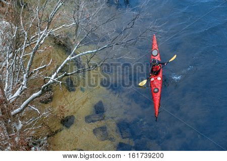 man paddles a red kayak on the river near the shore, kayaking