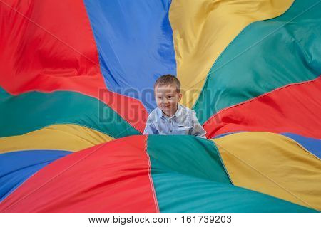 Portrait of white Caucasian child boy toddler sitting in the center of playground rainbow parachute celebrating his birthday at party