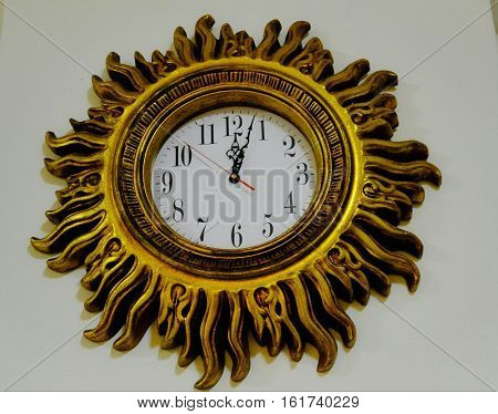Isolated image of golden clockface with sun rays design.