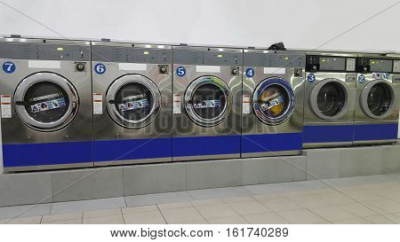 Rows of commercial industrial washing machines for public use