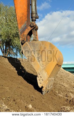 Bucket excavator to dig a hole. Summer.