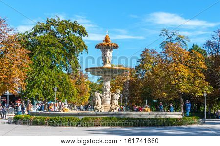 Madrid, Spain - November 9th, 2013:  Tourism in Spain.  A fountain is well attended in Retiro Park.  Man takes a photo.  Citizens and tourists alike, take advantage of beautiful weather conditions.