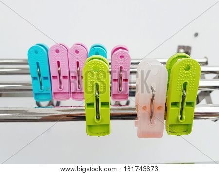 Isolated Colorful plastic clothespin / clothes pegs in rows on silver metal rail with white background