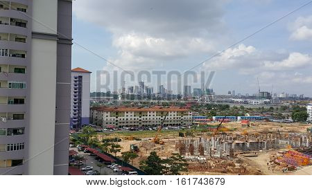 High angle view of cityscape with construction site, high rise buildings and mix urban development on sunny day