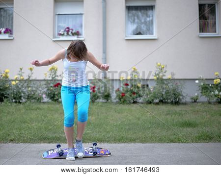 Girl teenager training ride on a skateboard summer day